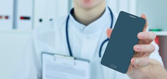 Male doctor`s hand showing a blank smart phone screen. stock image