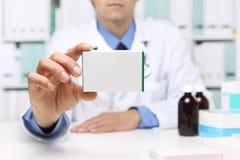 Doctor hand showing drug boxes at Office Desktop stock images