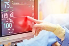 Doctor hand touch on electrocardiogram showing patient heart rat. E in emergency room at hospital with blur background stock images