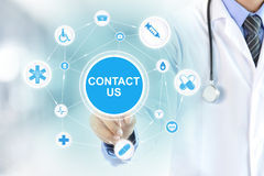 Doctor hand touching CONTACT US sign on virtual screen. Medical support and service concept Stock Photos