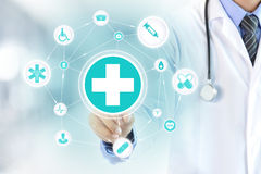 Doctor hand touching first aid sign on virtual screen. Healthcare and medical concepts Royalty Free Stock Photos