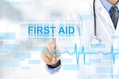Doctor hand touching FIRST AID sign on virtual screen Royalty Free Stock Image