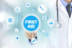 Doctor hand touching FIRST AID sign Royalty Free Stock Images