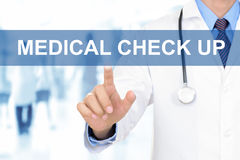Doctor hand touching MEDICAL CHECK UP sign on virtual screen. Doctor hand touching MEDICAL CHECK UP sign on blue virtual screen Royalty Free Stock Images
