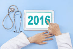 Doctor hand touching number 2016 on the tablet Stock Image