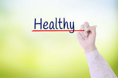 Doctor hand writing Healthy ,Healthy with marker on   on visual screen over green nature blurred background. Stock Images