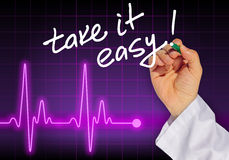 Doctor hand writing message TAKE IT EASY!. With heart rate monitor in the background Royalty Free Stock Image