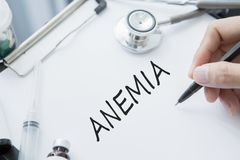 Doctor hand writing text of Anemia disease Stock Photo