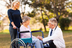Doctor handicapped woman. Male doctor talking with handicapped senior women at the retirement home Royalty Free Stock Images