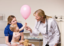 Doctor handing baby girl balloon Stock Photo