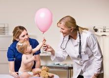 Doctor handing baby girl balloon. Doctor handing a balloon to a baby girl Stock Photo