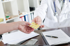 Doctor handing a blister of pills to his assistant Royalty Free Stock Images