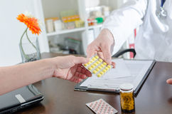 Doctor handing a blister of pills to his patient Stock Image