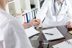 Doctor handing a bottle of pills to his assistant Royalty Free Stock Photography