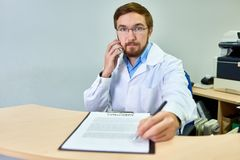 Doctor Handing Contract  to Patient. Portrait of friendly bearded doctor handing pen and contract to patient siting at desk in office and using smartphone Stock Images