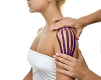 Doctor hands applying special physio tape on woman shoulder Stock Images