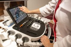 Doctor hands on control panel with keyboard of medical ultrasound diagnostic equipment in clinic. Close up stock photo