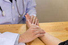 Doctor hands feeling pulse on female wrist Royalty Free Stock Photography