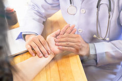 Doctor hands feeling pulse on female wrist. Doctor measuring pulse of his senior patient. healthcare and medical concept Stock Photo