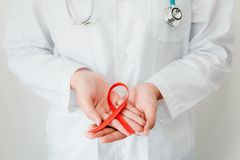 Doctor Hands is Holding Red Ribbon, AIDS, HIV International Symbol of Awareness, Healthcare and Medicine Concept. Close-Up of. Female Medicine in Lab Uniform royalty free stock photo