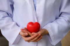 doctor hands holding red toy heart Stock Photo