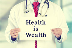 Doctor hands holding white card sign with health is wealth text message. Closeup doctor hands holding white card sign with health is wealth text message isolated Royalty Free Stock Photography