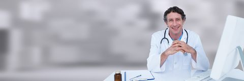 Doctor hands together at desk against white blurred background Royalty Free Stock Image