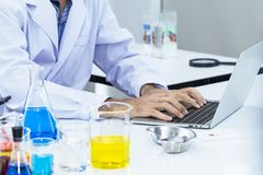 Doctor hands typing on computer keyboard near test tube at lab. Oratory.Copy space stock photography
