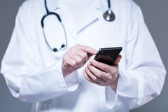 Doctor hands using mobile phone Royalty Free Stock Image