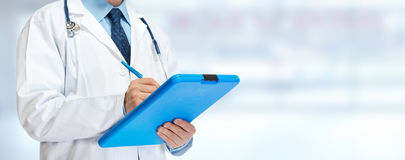 Doctor hands writing on clipboard. Medical doctor pharmacist hands writing prescription over blue background Stock Photo