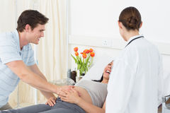 Doctor with happy expectant couple Stock Photo