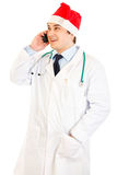 Doctor in hat of Santa Claus talking on mobile Royalty Free Stock Photography