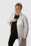 Doctor having a check up. Short hair blond caucasian forties female doctor  holding stethoscope and listening to her own heart over white background Stock Image