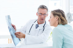 Doctor having conversation with his patient and holding xray Stock Images