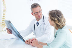 Doctor having conversation with his patient and holding xray Royalty Free Stock Photos