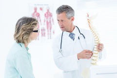 Doctor having conversation with his patient and showing spine model Stock Photo
