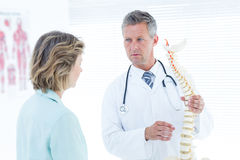 Doctor having conversation with his patient and showing spine model Royalty Free Stock Photo