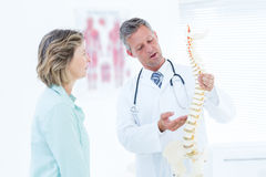 Doctor having conversation with his patient and showing spine model Royalty Free Stock Images