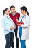 Doctor having conversation with pregnant couple. Happy doctor having conversation and giving explanations to a pregnant woman and her husband isolated on white Royalty Free Stock Photography