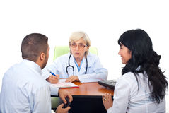 Doctor having conversation with young couple Royalty Free Stock Images