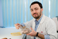 Doctor having a lunch at his office during the break. Employee eating buckwheat from lunchbox plastic container Stock Images