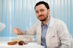 Doctor having a lunch at his office during the break. Employee eating buckwheat from lunchbox plastic container Stock Photo