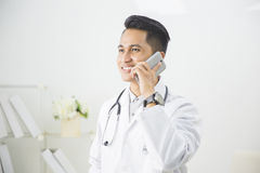 Doctor having phone call at his medical office Stock Photo