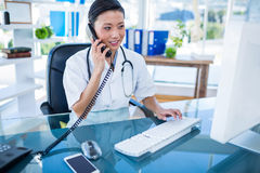 Doctor having phone call and using her computer Stock Photos