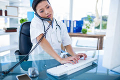 Doctor having phone call and using her computer Royalty Free Stock Images