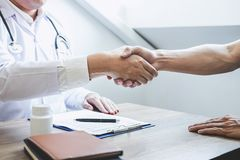 Doctor having shaking hands to congrats with patient after recommend treatment while discussing explaining his symptoms and royalty free stock photography