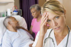 Doctor With Headache In Patients Room. On Hospital Ward royalty free stock image