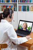 Doctor headphones laptop patient agony. Doctor at a pain management center in her office with headset and laptop, listening to patient in agony with strong royalty free stock photography