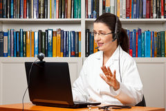 Doctor headset computer webcam talking. Doctor sitting with a headset or headphone at her desk in front of a computer with an attached camera and talking Royalty Free Stock Photos
