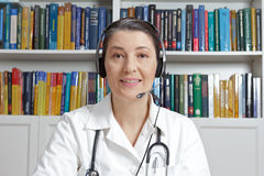Doctor headset talking online consultation. Doctor or general practitioner with headset in surgery office talking online with a patient, as seen through a webcam Stock Image